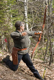 Senior woman shooting with a traditional bow Stock Photos