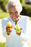 Senior Woman Shooting Water Pistols Stock Images