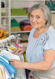 Senior woman in shop. Portrait of a senior woman choosing shirt in shop Royalty Free Stock Image