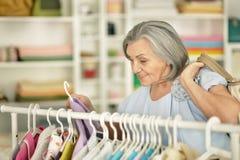 Senior woman in shop. Portrait of a senior woman choosing shirt in shop Stock Photography