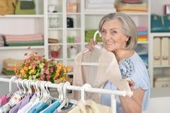 Senior woman in shop. Portrait of a senior woman choosing shirt in shop Stock Image