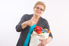 Senior woman with shopping bag and credit card showing thumbs up, paying for shopping stock image