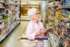 Senior woman with shopping list. In supermarket Royalty Free Stock Photo