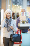 Senior Woman Shopping In Mall As Husband Carries Boxes Stock Image