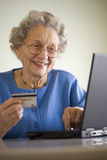 Senior woman shopping online. Smiling senior woman using credit card and laptop Stock Image