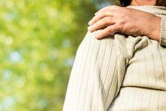 Senior woman with Shoulder Pain. Senior woman Shoulder Pain. Bokeh background, public park stock image