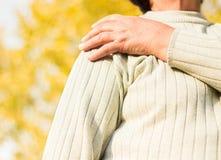 Senior woman with Shoulder Pain. Senior woman Shoulder Pain. Bokeh background, public park stock photo