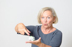 Senior Woman Showing Crumpled Money on Hand Stock Photo