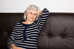 A  senior woman showing that she enjoys retirement. A  senior woman showing that she enjoys retirement by relaxing Royalty Free Stock Photos
