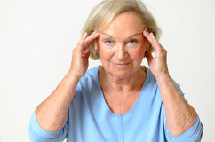 Senior woman showing her face, effect of aging. Senior woman wearing blue shirt while showing her face, effect of aging caused by loss of elasticity, close-up Stock Image