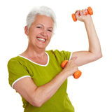 Senior woman showing off her. Happy senior woman with dumbbells showing off her muscles Royalty Free Stock Photography