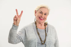 Senior woman showing peace gesture. royalty free stock images