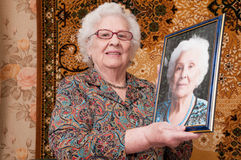 Senior woman shows her portrait Royalty Free Stock Image