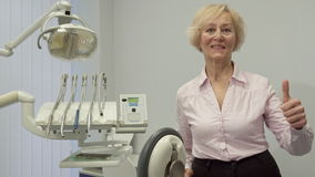 Senior woman shows her thumb up at the dentist office stock video footage
