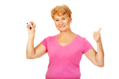 Senior woman shows thermometer and gesturing OK Royalty Free Stock Photography