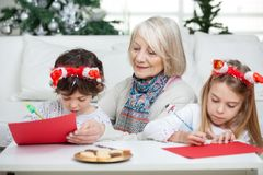 Senior Woman With Siblings Writing Letters To Stock Image