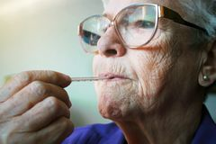 Senior woman sick. Senior woman with thermometer in her mouth Stock Image