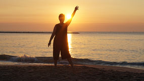 Senior woman silhouette raising hand in front of new day ornage Royalty Free Stock Image