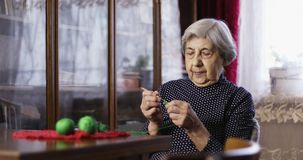 Senior woman sits and knits. Old woman is engaged in knitting. Craft. Hobby stock video footage