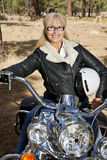 Senior woman sits on motorbike with forest in background Stock Photography