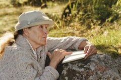 Senior woman sits outdoors reading a book Royalty Free Stock Image