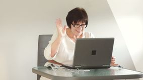 Senior woman sits by the table with laptop. Using computer talking via messenger app Skype. Smiling waving hand in stock video