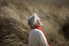 A senior woman sitting amongst the sand dunes, enjoying the sun Royalty Free Stock Photography