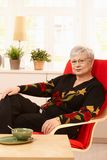 Senior woman sitting in armchair Stock Photography