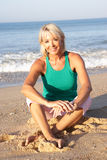 Senior woman sitting on beach relaxing Royalty Free Stock Photo