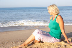 Senior woman sitting on beach relaxing Stock Photo