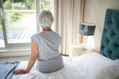 Senior woman sitting on bed in bedroom stock images