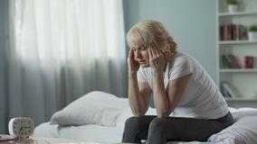 Senior woman sitting on bed and suffering from terrible headache, health problem. Stock footage stock video footage