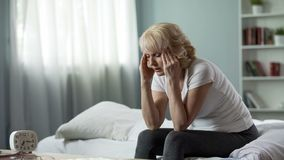 Senior woman sitting on bed and suffering from terrible headache, health problem. Stock photo stock photography