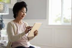 Senior Woman Sitting On Bed Using Digital Tablet Royalty Free Stock Photos