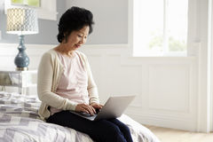 Senior Woman Sitting On Bed Using Laptop Computer Stock Images