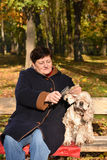 Senior woman sitting on a bench with a dog Stock Photography