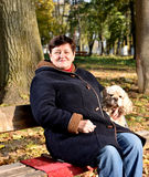Senior woman sitting on a bench with a dog Stock Images