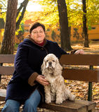 Senior woman sitting on a bench with a dog Stock Image