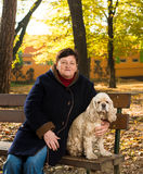 Senior woman sitting on a bench with a dog Royalty Free Stock Photos