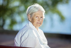 Senior woman sitting on bench in park Royalty Free Stock Image