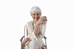 Senior woman sitting in camping chair holding drink, cut out Stock Photos
