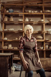 Senior woman sitting on chair against shelves with pottery goods Royalty Free Stock Photo