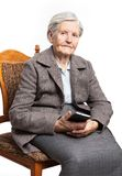 Senior woman sitting on chair and holding phone Stock Photos
