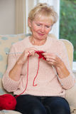 Senior Woman Sitting In Chair Knitting Stock Photography