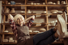 Senior woman sitting on chair with legs on table against shelves with pottery goods. Front view of senior woman sitting on chair with legs on table against Stock Photography
