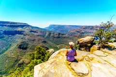 Senior woman sitting on a cliff`s edge, enjoying the view of the Blyde River Canyon from the viewpoint at the Three Rondavels stock photography