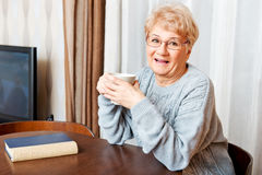 Senior woman sitting at the desk with book and drinking tea or coffee Stock Photography