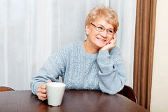 Senior woman sitting at the desk and drinking coffee or tea Stock Image
