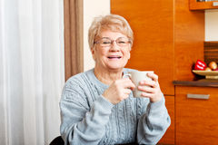 Senior woman sitting at the desk and drinking coffee or tea Royalty Free Stock Photos