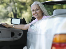 Senior woman sitting in driver's seat of convertible car, smiling, portrait Royalty Free Stock Photo